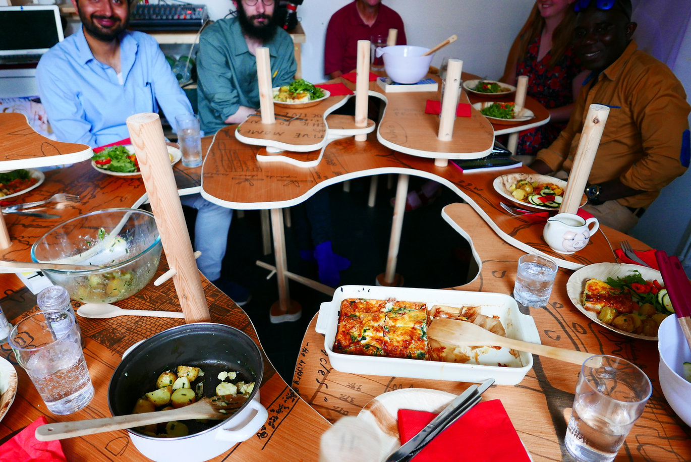 A group of people sitting around a wiggly table with food on plates and napkins.