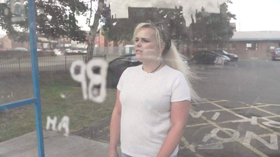 A person stands behind a piece of perspex with initials carved into it in a carpark