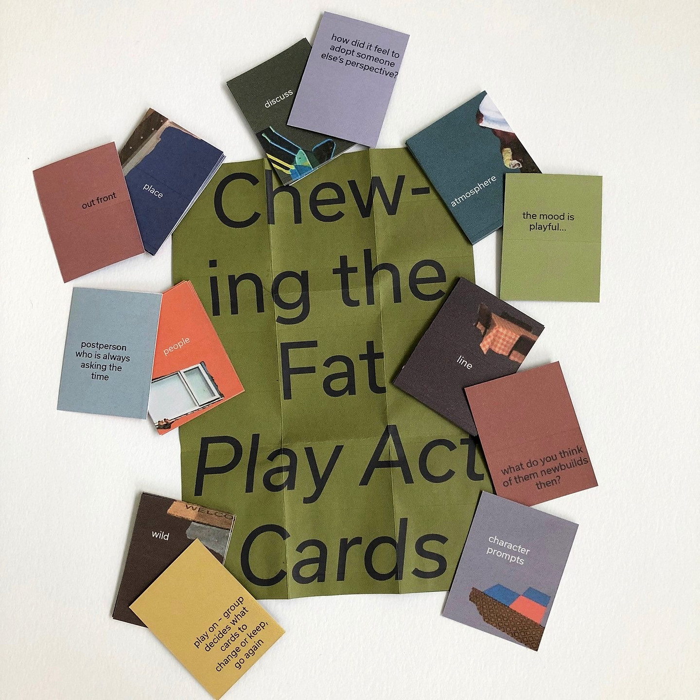 A set of colourful palm sized playing cards are scattered around a mushy pea green set of instructions tha read: Chewing the Fat, Play Act Cards in bold across a folded out set of instructions. The colour scheme is bright but muddy and the cards have words such as 'people' 'place' and 'line' on them as well as descriptions relevant to these such as 'postpersn who is always asking the time' and ' what do you think of the newbuilds?'. They also have digitally collaged images on the such as a cafe table, or a house window or toys usually found in 'everyday' urban life.