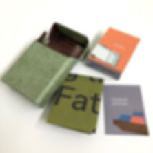 The open re-purposed 'fag packet' is pictured with its contents laid out nearby. There is a small pile of small cards. The one on top reads 'people' and has the icon of a window with a pair of shoes on the roof outside the window digitally collaged on to it. The mushy pea instructions from previous image are folded up small so that you can only read the word: 'Fat'. Another card is next to this that is a soft,muddy purple. It reads: 'character prompts' and has a little icon which is a digitally collaged fragment of a 80s pub carpet with a play mat on top. The kind that is like a giant square jigsaw. This is blue and red.