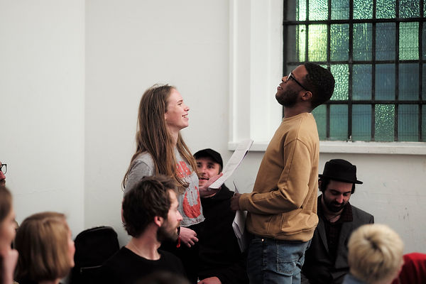 Image shows two performers in a white walled gallery. They are amoungst a crowd who are an audience and are listening. The actors are in their mid 20s, one white female, one black man. They are both holding scripts and appear to be laughing, sharing a joke or funny story.