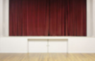 Image description: facing heavy dark red velvet curtains hanging on a stage. The stage edges are white and there are two small doors under the stage. The floor is visible n the foreground an is floorboards wih gym markings.