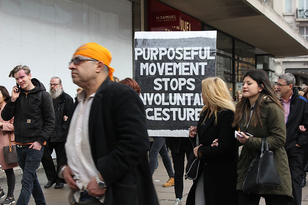 Image is taken on a busy shopping street in London. A diverse mix of people of different ages, ethnicities and genders walk past. Some turn to look back at a large placard that reads: 'Purposeful Movements Stops Involuntary Gesture' that is held up by someone who stands behind the sign. The sign is black and white and appears handmade with marker pens and is in very bold capitals. It measures approx 1.5x1m.