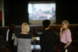 A group of people stand in front of a screen talking, the screen is on the back of a stage at the Working Men's Club, and is playing the Idle Acts Film. The screen shows a goup of actors sitting together around a table.