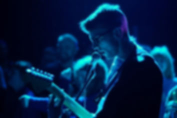 Image Description: A close-up of Giles backlit by a blue light, his figure dramatically silhouetted whilst the audience is in the background, out of focus.