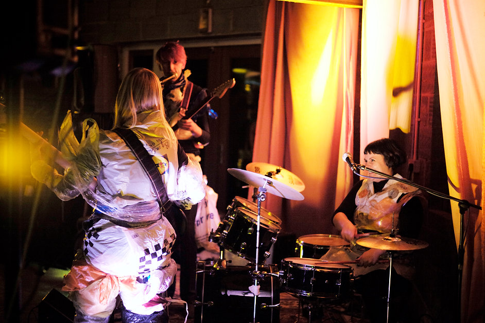 A warm, saturated photograph depicting the band playing at Noisy Night in Sussex. Giles is on guitar, looking serious, Kerri on drums looking happy and Sophie wit her back towards the camera, emphatically finger picking her bass.