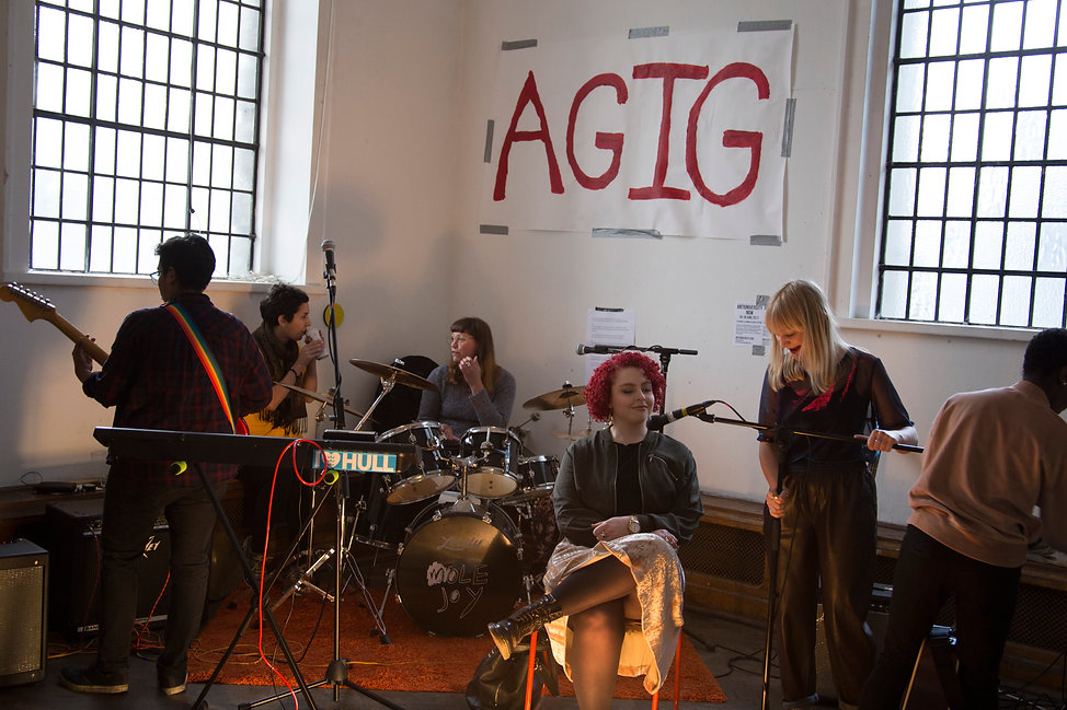 Image Description: A band setting up for practice, in front of a large banner taped to the wall which reads 'AGIG'.