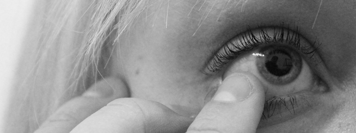 Image description: image is a black and white photograph. It is a close up of someone's eye with a finger touching the pupil.