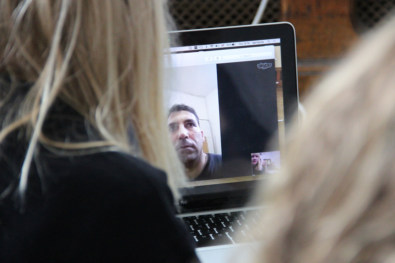 Image Description: Two women skyping a man on a laptop.