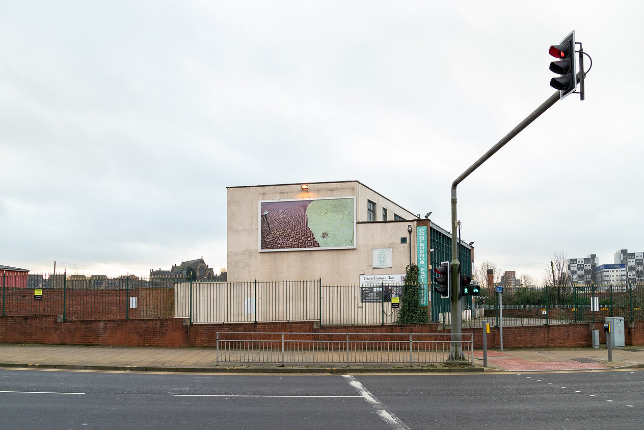 Photograph of a billboard from across the street on the sie of a building, on the billboard is a photo of a pub carpet collaged with a photo of the ground in a playground. In the foreground is a road and railings. The sky is quit grey and you can see brick buildings in th background.