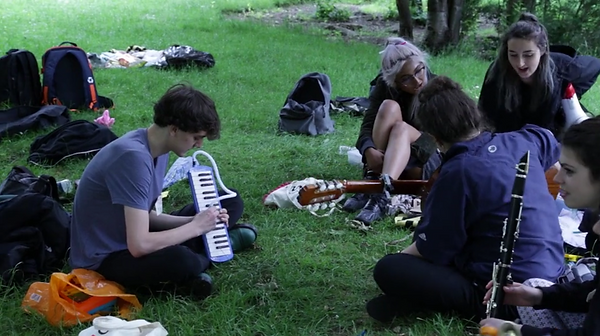 Image is of a group of people sitting on somevery green grass what appears to be under a tree, in a park. There are different bags strewn around them and most of them have instruments in their hands. Acoustic guitar, small air melodica keyboard, clarinet and megaphone. There are 5 people facing at different angles. The two women furthest away are reading something singing.