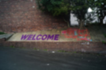 Photograph of a mural painted on a slanted concrete wall next to tall brick sie of a houe and trees. The mural says WELCOME in large purple letters and the drawing on the right of it depicts colourful shapes and the sillouette of groups of people painted in red.