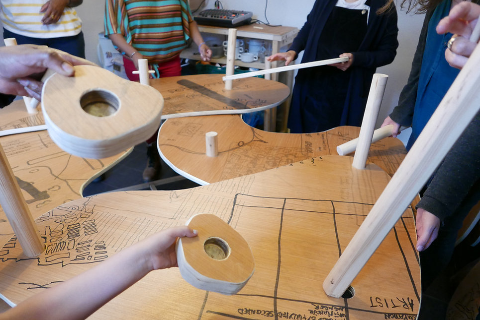 Photograph of the sculpture / table being put together showing lots of peole's hands holding different parts.