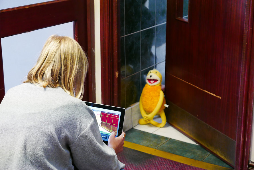 Photograh of Sophie crouched down holding an Ipad taking a photo of a cuddley toy at the entrance of the men's toilets at the club.