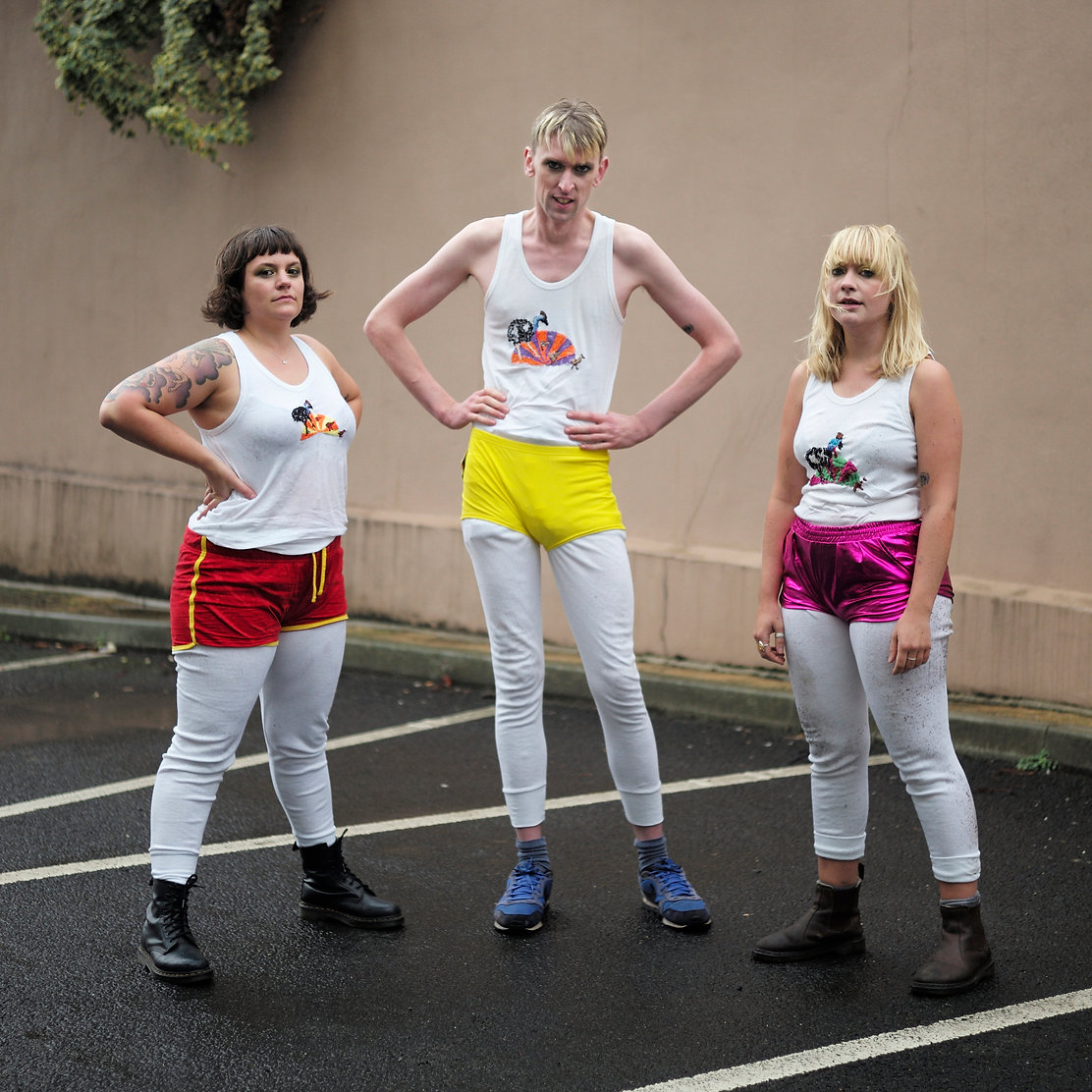 A photo of the band in a car park, Kerri on the left, Giles in the middle and Sophie on the right. They wear intense expressions, decked out in neon shorts over white leggings and vests.