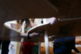 Photograph from underneath the table, people looking between th gaps from above and attaching pegs for support.