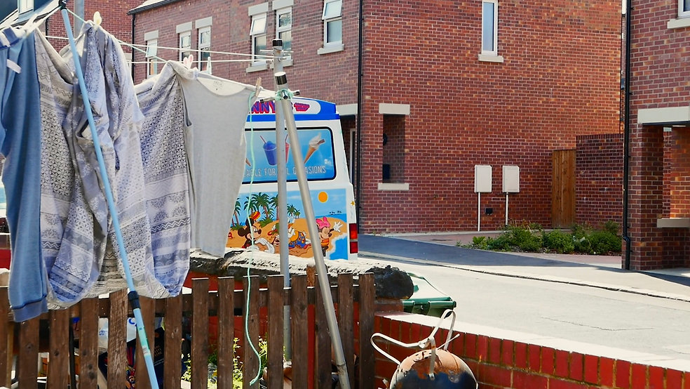 An ice cream van is parkd down a street with red brick houses, washing is hung on the line in the foreground