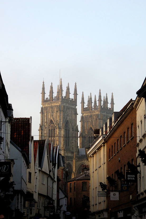 Looking down an old street in the city of York. In the background, slightly obscured by mist, the towers of York Minster rise above the building-tops.