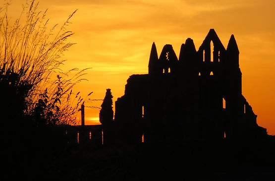 The ruins of the Whitby Abbey at sunset. The abbey stands etirely in shadow, lit from behind by a blazing orange sky.