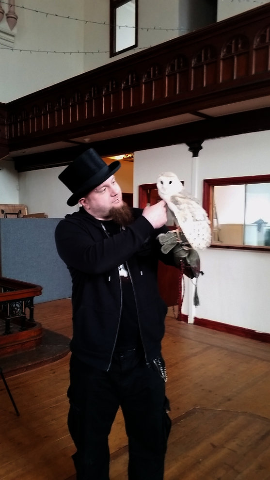 Author Sean Walter standing to the side of our front presentation table, holding a white and grey barn owl. The owl's name is Dobby the House Owl. Sean, standing in a black top hat, a black zip-up hoodie, black t-shirt, and black trousers, is stroking Dobby's neck. Dobby, unconcerned, is watching the camera.