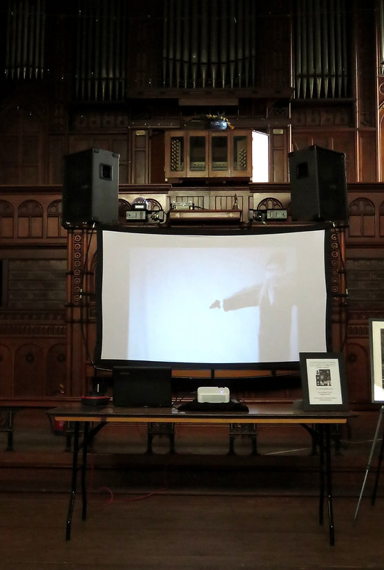 A pulpit in an old church, set up with speakers and musical equipment for the evening party events. In the foreground, a projector and screen showing a stop-motion movie made for the tour. Behind it, taking up the entire back wall, a massive pipe-organ stands in shadow.