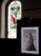 """In the foreground, right, the original charcoal artwork for """"Timber"""" hangs on a chain attached to our free-standing, black-clad show stands. In the background, left, sun shines through a stained glass window with prominent religious symbolism."""