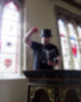 Sean Walter standing in a pulpit, holding a copy of Tales in Sombre Tones, with a glass of red wine in front of him. He's reading from the book, his face a contorted caricature of zealousness. High right fist is in the air. In the background, several stained glass windows have light shining through them.