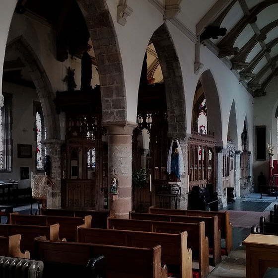 A view from the back of All-Saints Church. Several wooden pews sit in neat rows, the paths between them paved with ancient grave markers with words chiseled in latin. The stone pillars and arches mark this as a truly ancient structure.