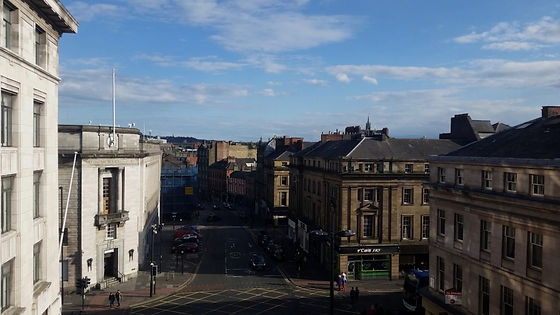 A cityscape view from Vane Gallery showing Newcastle-upon-Tyne under a blue sky.