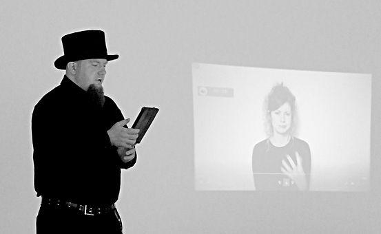 A grey-scale image. Sean Walter stands to the left, reading aloud from his tablet in a top hat, black shirt, and black pants. In the background, a video of the British sign langage interpretation of the reading plays.