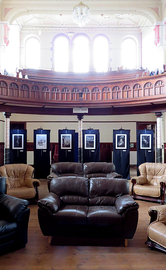 The interior of The Brunswick Centre on show day. Leather chairs and sofas sit in the middle of an old church, sun shining in through the balcony windows above. All around the room, different images from Tales in Sombre Tones are hanging on chains on black, cloth backgrounds.