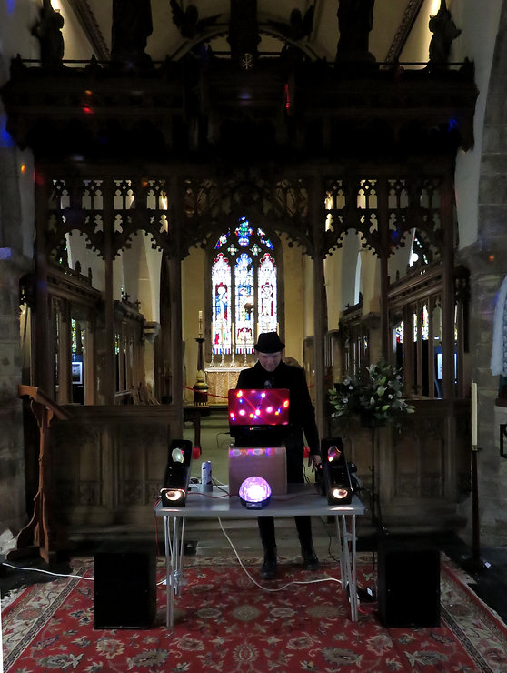 Our DJ, Jay, standing in front of his music setup, in front of a large, ornate, wooden archway. A laser-bal shows bright pink lights on most of his equipment.