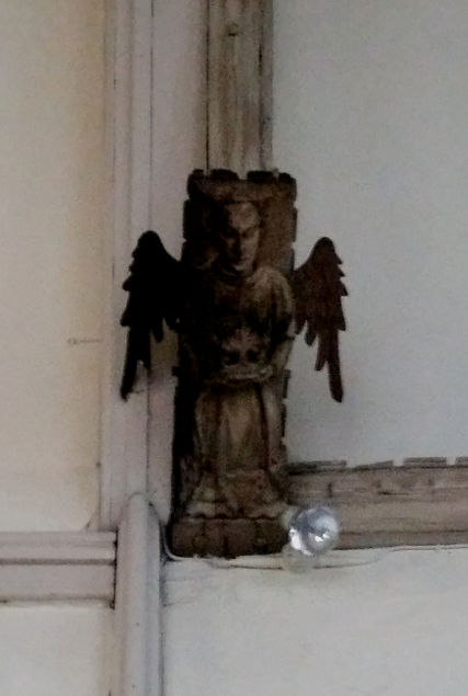 A carved, wooden angel carrying an unknown object with it. The left side (from the veiwer) of the angel is charred and burned, while the right side is the color of fresh clay.