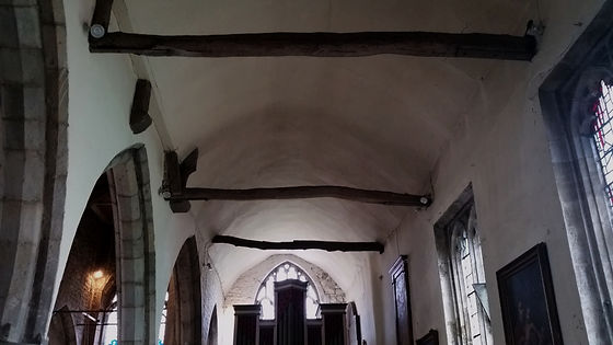Several ancient oak branches, bent and gnarled, being used as support joists in the cieling of All-Saints. In the background, almost out of the shot, is the top of their small pipe-organ.