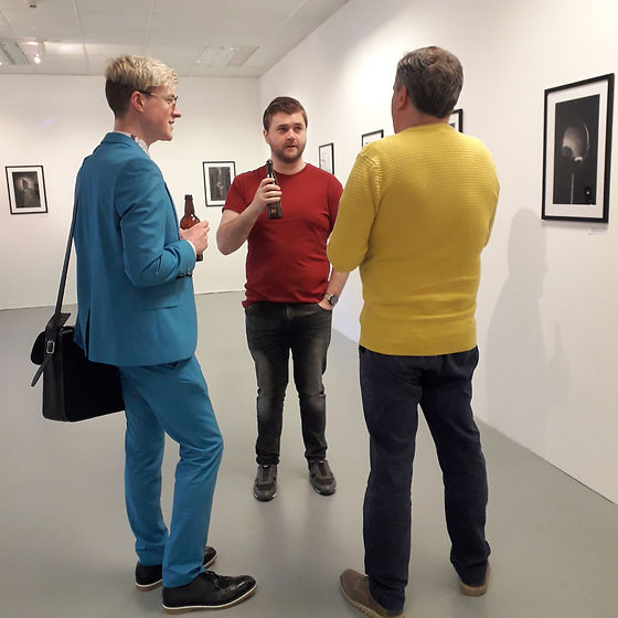 Three men stand in front of the artwork, dark bottles in their hands. They seem to be discussing the artwork.