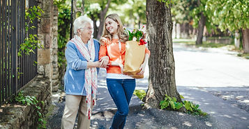 Person helping older person with groceries. Home care.