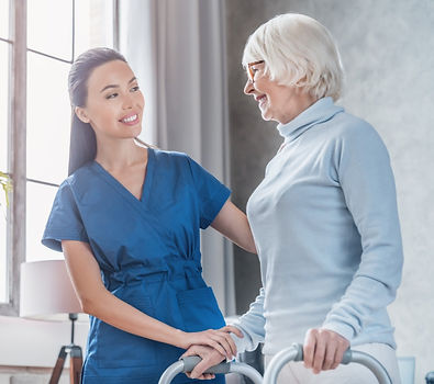 Person in a walker receiving help from a personal support worker.