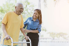 A personal support worker helping a person walk after they've had a stroke.