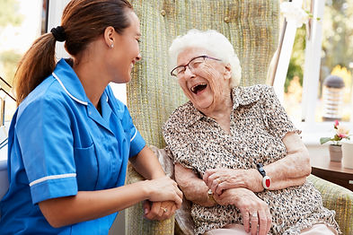 Laughing, happy elderly woman and personal support worker.