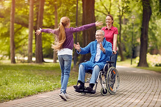 Happy grandfather in a wheel chair being pushed by a personal support worker.