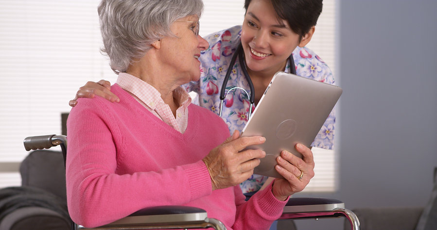 Elderly woman happily talking with her home care nurse.