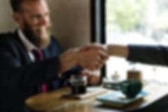 Der Kunde trifft die Werbetexterin für ein Beratungsgespräch in einem Cafe. Er ist sichtlich zufrieden und genießt die entspannte Atmosphäre und die kompetente Beratung.