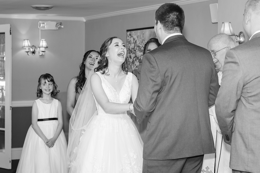 Bride laughing during wedding ceremony black and white flower girl smiling in Maine Country Club