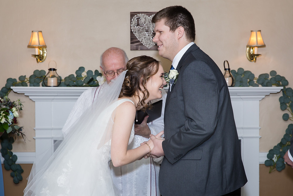 Bride and Groom laughing at wedding ceremony in front of fireplace at their wedding