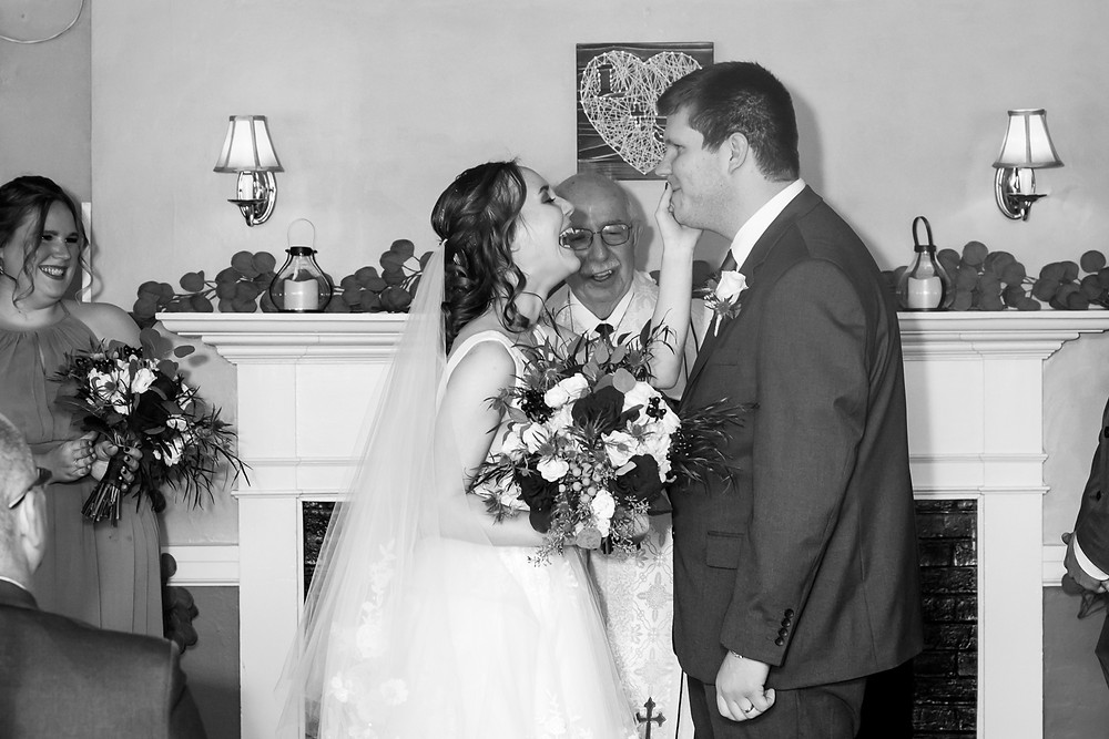 Bride and Groom laughing at ceremony being photographed by Julie Frances Photography