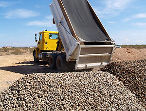 A dump truck is dumping gravel on an exc