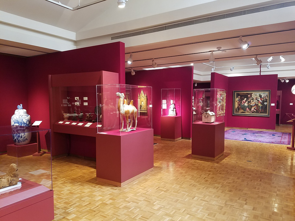 A wide-set angle looking into a museum exhibit of ancient cultural artifacts in glass cases.