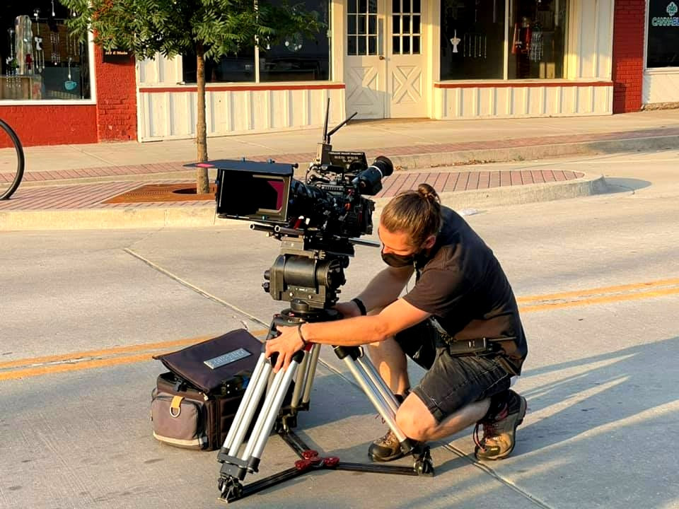 A man crouches in an empty street setting up a large camera in front of an art gallery.