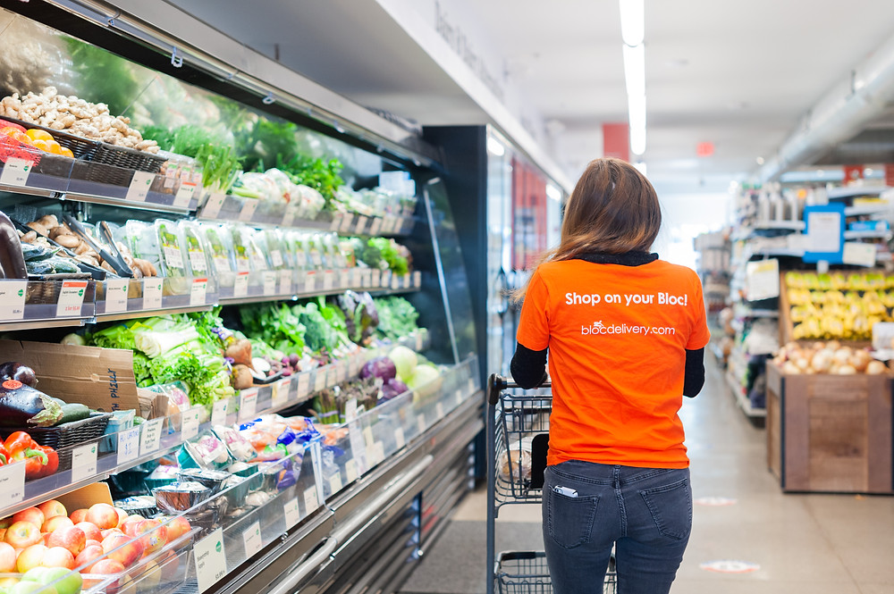 """person pushing a shopping cart down the produce aisle wearing orange shirt that reads """"shop on your bloc""""."""