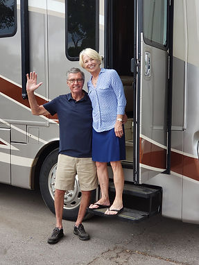 Husband and wife are waving goodbye just before they leave on vacation in their RV rental from Mid Florida RV.